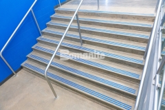 "The Bomanite Modena SL Custom Polishing System was utilized on several sets of concrete steps at Grain Valley High School and features a three-line nose detail that was engraved into the concrete and filled with ""Grain Valley Blue"" epoxy to provide a distinct design element that showcases the school's colors."