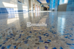 The entrance hallway at Grain Valley High School was renovated by installing a Bomanite Modena SL topping slab that contains two shades of vibrant blue glass aggregate and eye-catching pieces of sparkling mirror glass and this custom polished surface adds unique detail while embodying the school's colors and team spirit.