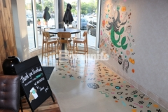 Bomanite Modena SL was used inside this Starbucks to create a polished, highly durable cementitious overlay that was selected as a low-cost concrete flooring alternative and adds a simple, elegant finish that serves as the perfect backdrop for this playful and colorful mural.