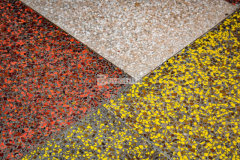 Bomanite Revealed decorative concrete incorporates a unique binder and color blending process with specialty aggregates and in this case included solid glass aggregates in white, black, red, and yellow set in a diamond pattern with brass divider strips to set apart the different colors of glass aggregates and provides a vibrant and durable finish.