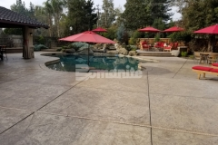 This beautiful backyard pool deck and patio were cast-in-place and stamped with the Bomacron Slate Texture imprint pattern and the addition of Bomanite Sand Color Hardener and Bomanite Light Brown Release Agent created a natural design aesthetic that fits in perfectly in this backyard oasis.